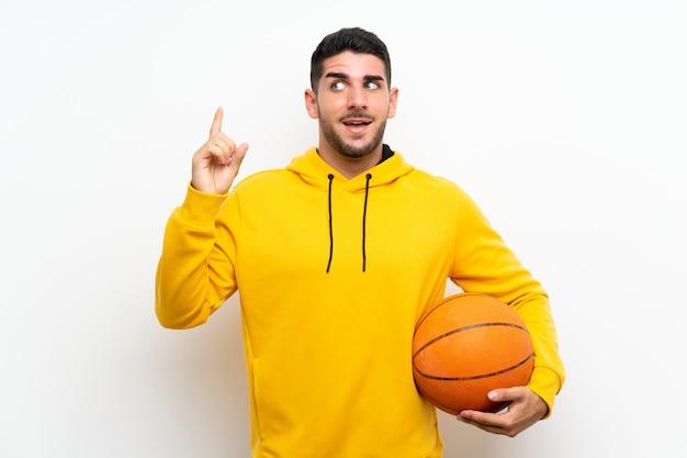 Beau jeune homme de joueur de basket sur un mur blanc isolé destiné à réaliser la solution tout en levant un doigt