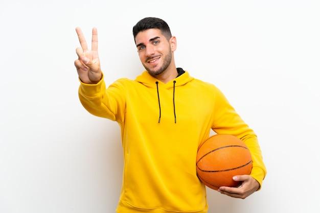 Beau jeune homme de joueur de basket sur mur blanc isolé, souriant et montrant le signe de la victoire