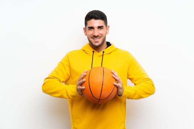 Beau jeune homme de joueur de basket sur un mur blanc isolé