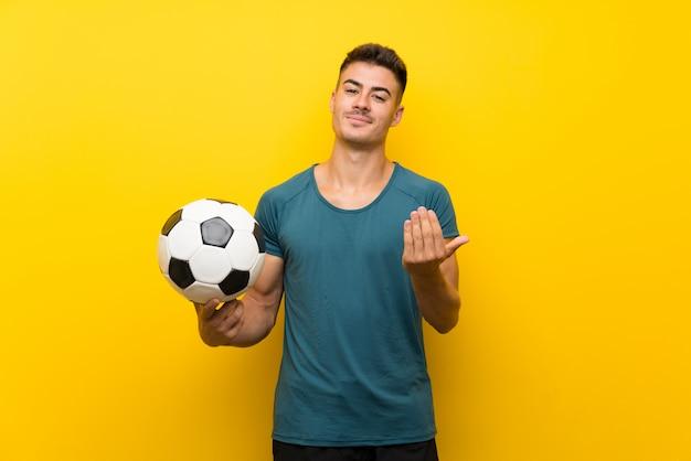 Beau jeune homme joueur de football au mur jaune invitant à venir avec la main. heureux que tu sois venu