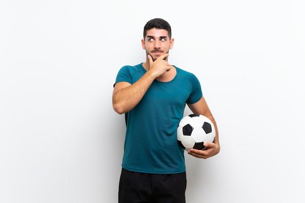 Beau jeune homme joueur de football sur mur blanc isolé, pensant une idée