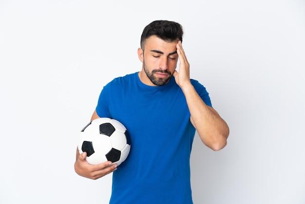 Beau jeune homme joueur de football sur mur isolé avec maux de tête