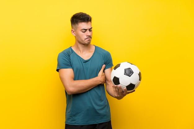 Beau jeune homme joueur de football sur un mur jaune avec une expression triste