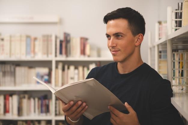 Beau jeune homme lisant à la bibliothèque