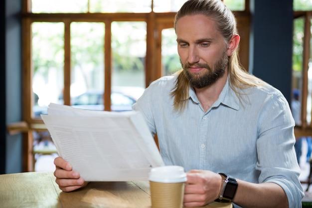 Beau jeune homme lisant le journal à table dans un café
