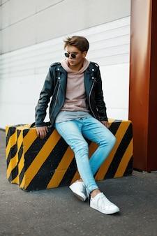 Beau jeune homme avec des lunettes de soleil dans une veste en cuir noir, un jean bleu et des baskets blanches est assis sur une dalle noire et jaune