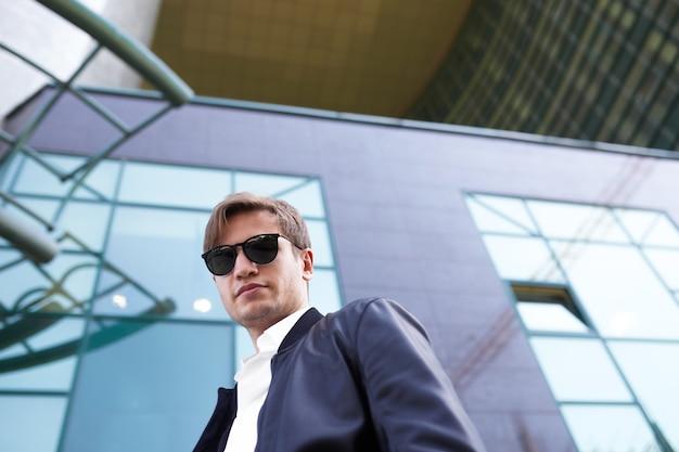 Beau jeune homme à lunettes de soleil. portrait masculin en plein air.