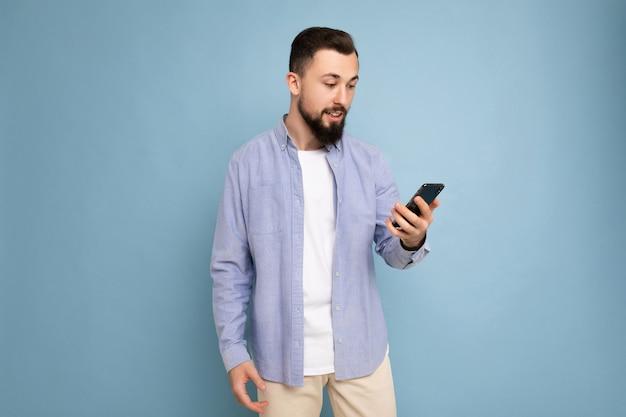 Beau jeune homme mal rasé brune avec barbe portant un t-shirt blanc élégant et une chemise bleue isolée