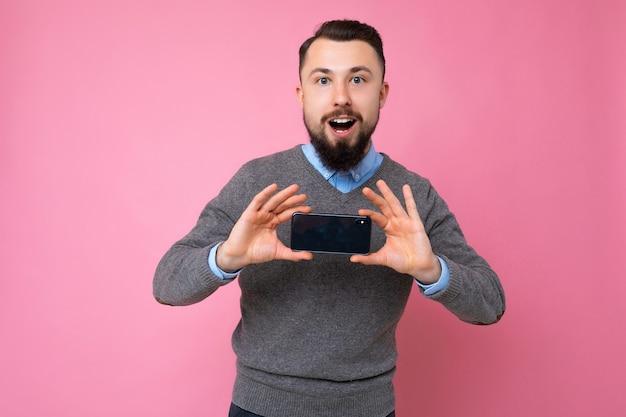 Beau jeune homme mal rasé cool et heureux avec un pull gris élégant et une chemise bleue debout isolé sur un mur de fond rose tenant un smartphone et montrant un téléphone avec un écran vide