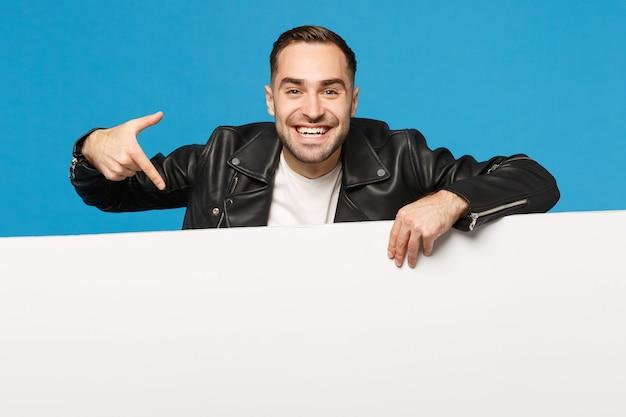 Un beau jeune homme mal rasé tient un grand panneau d'affichage blanc vide pour le contenu promotionnel isolé sur un portrait de studio de fond de mur bleu. concept de mode de vie des émotions sincères des gens. maquette de l'espace de copie