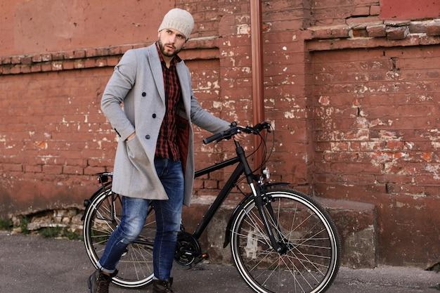Beau jeune homme en manteau gris et chapeau poussant son vélo dans une rue de la ville.