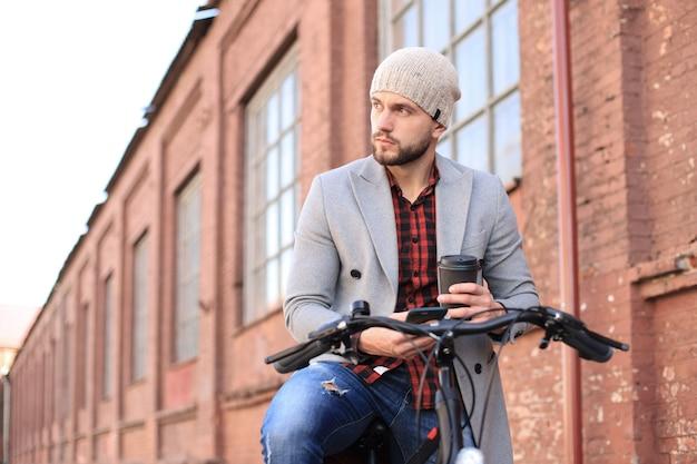 Beau jeune homme en manteau gris et chapeau regardant le téléphone alors qu'il était assis sur son vélo.
