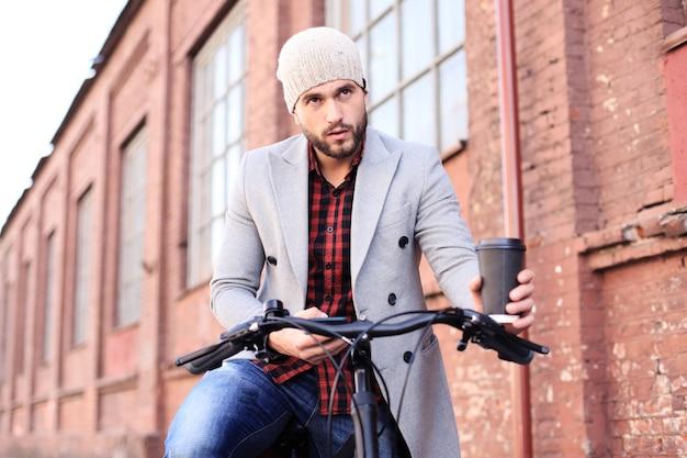 Beau jeune homme en manteau gris et chapeau et regardant le téléphone tout en poussant son vélo à côté de lui.