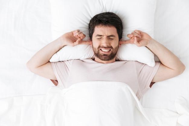 Beau jeune homme le matin sous une couverture dans le lit se trouve faire couvrir les oreilles