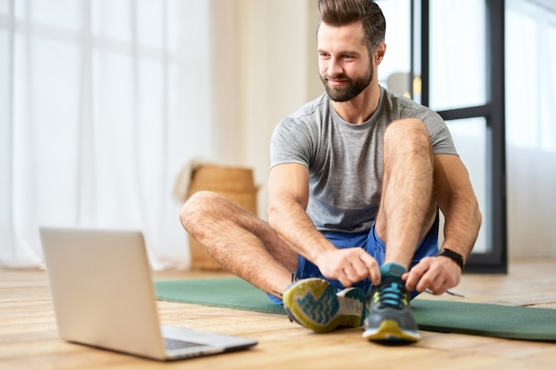 Beau jeune homme mettant des baskets et utilisant un ordinateur portable