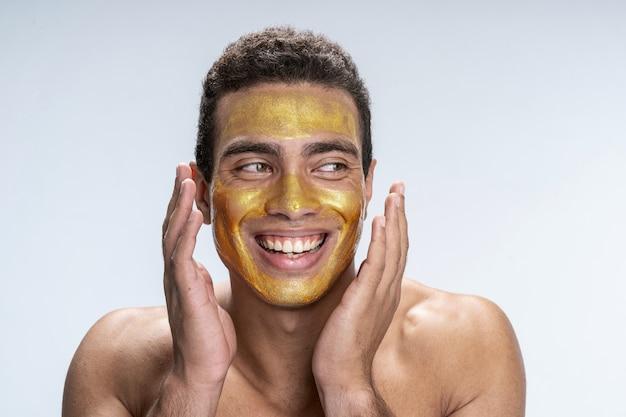 Beau jeune homme mettant un masque facial sur son visage