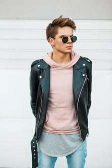Beau jeune homme à la mode avec une coupe de cheveux à lunettes de soleil dans une veste en cuir noir et un sweat-shirt rose près d'un mur en métal blanc