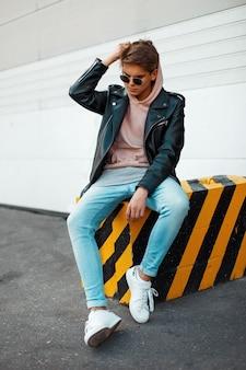 Beau jeune homme à la mode avec des lunettes de soleil dans une veste en cuir noir, un jean bleu et des baskets blanches met sur une capuche assis sur un noir et jaune