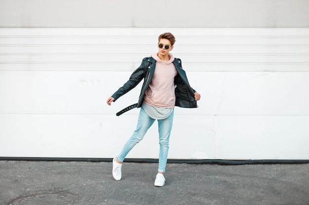 Beau jeune homme à la mode avec des lunettes de soleil dans une veste en cuir noir, un sweat-shirt rose, un jean de marque bleu et des chaussures blanches en mouvement
