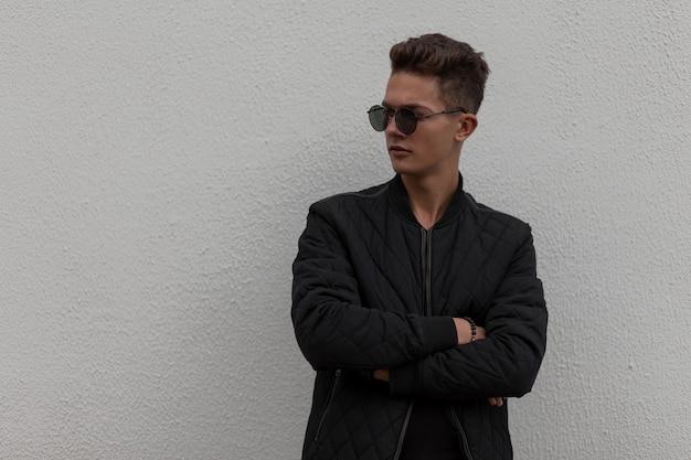 Beau jeune homme à la mode avec des lunettes de soleil élégantes dans des vêtements noirs à la mode avec une veste se dresse près du mur gris