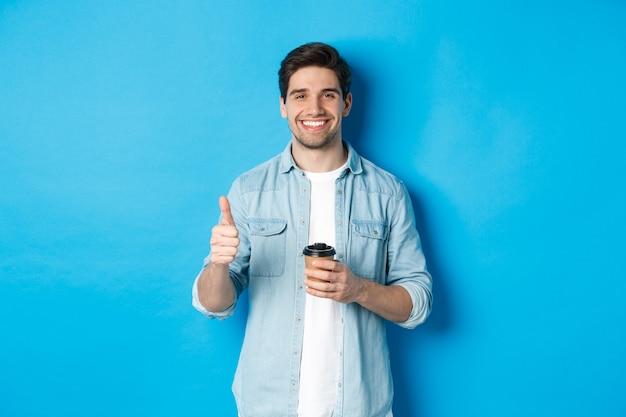 Beau jeune homme montrant le pouce vers le haut et buvant du café, recommandant des plats à emporter au café, debout sur fond bleu.