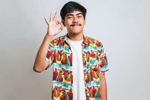 Beau jeune homme avec moustache portant un tshirt décontracté sur fond blanc souriant positif faisant signe ok avec la main et les doigts. expression réussie.