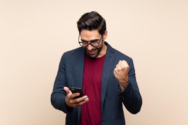 Beau jeune homme sur un mur isolé surpris et envoyant un message