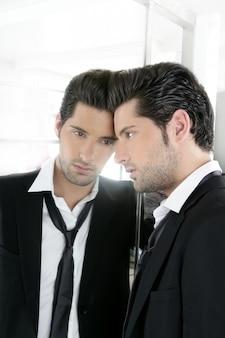 Beau jeune homme narcissique regardant dans un miroir
