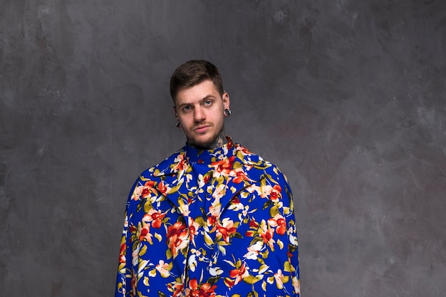 Beau jeune homme avec nez percé et oreilles portant un manteau floral sur fond gris