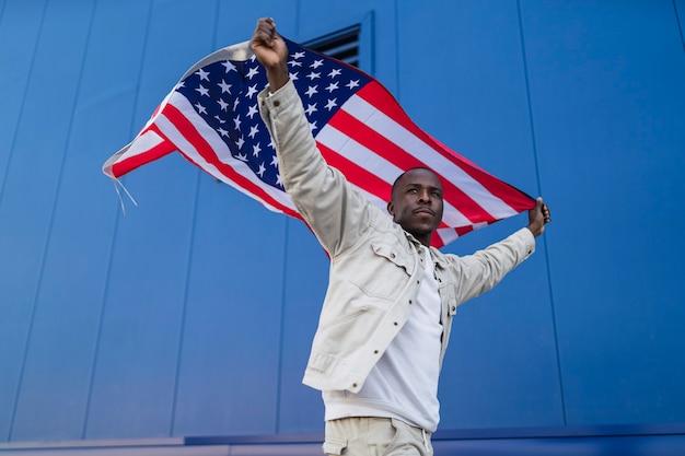Beau jeune homme noir avec le drapeau américain sur la tête à l'occasion du 4 juillet