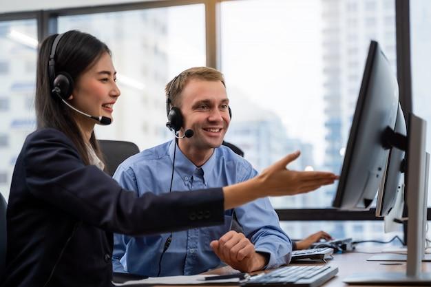 Beau jeune homme opérateur de centre d'appel et collègue portant des écouteurs travaillant sur ordinateur et parlant avec le client avec un esprit de service