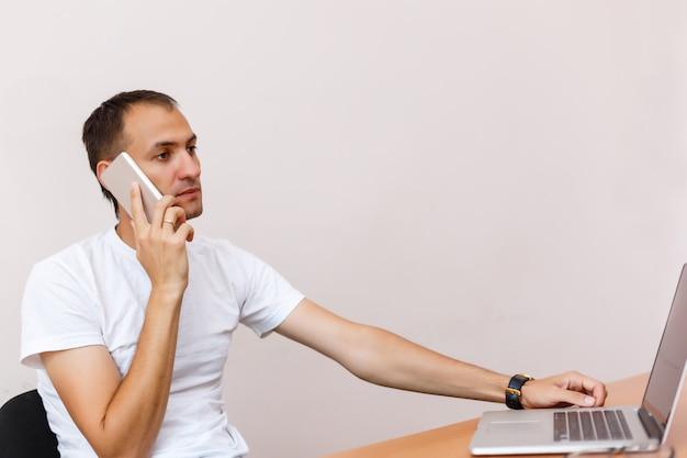 Un beau jeune homme avec un ordinateur portable sur fond gris