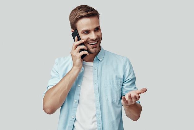 Beau jeune homme parlant au téléphone et souriant en se tenant debout sur fond gris
