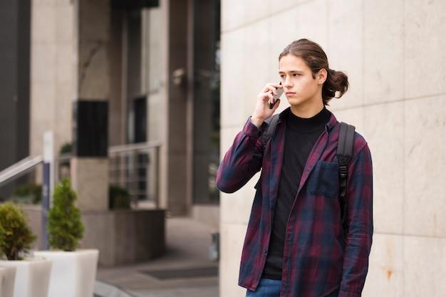 Beau jeune homme parlant au téléphone