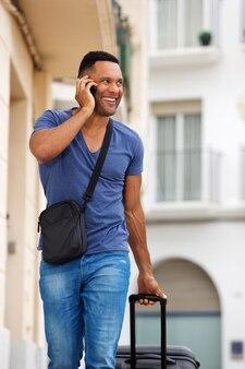 Beau jeune homme parlant sur un téléphone portable avec un sac