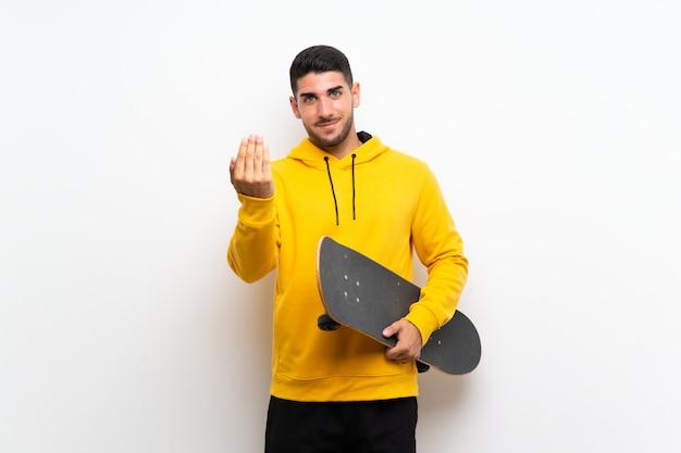 Beau jeune homme de patineur sur mur blanc invitant à venir avec la main