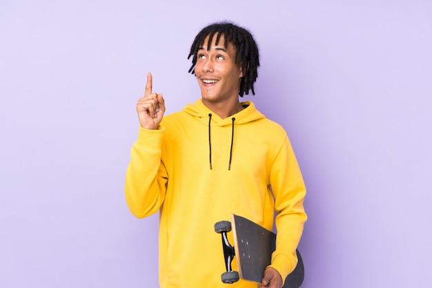 Beau jeune homme patineur sur un mur isolé ayant l'intention de réaliser la solution tout en levant un doigt