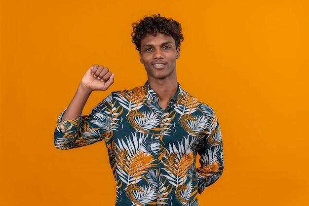 Un beau jeune homme à la peau sombre avec des cheveux bouclés en chemise imprimée de feuilles souriant levant la main avec le poing fermé