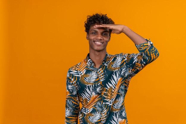 Un beau jeune homme à la peau sombre avec des cheveux bouclés en chemise imprimée de feuilles en souriant et avec la main sur la tête