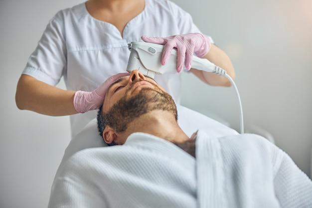 Beau jeune homme en peignoir allongé sur un lit de repos tout en recevant un traitement facial au laser dans une clinique cosmétologique
