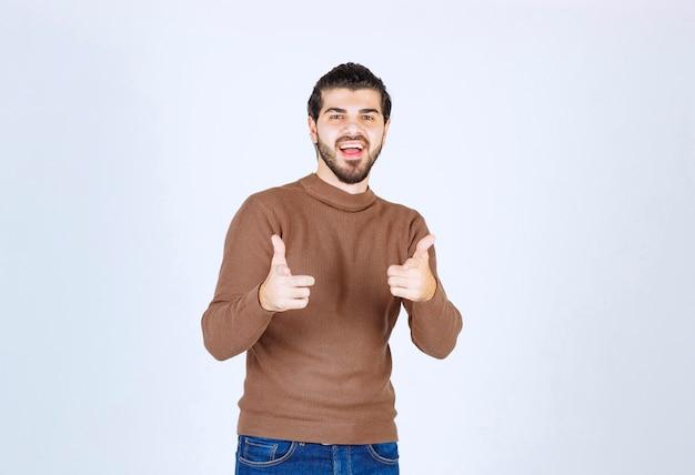 Beau jeune homme pointant vers la caméra et souriant. photo de haute qualité