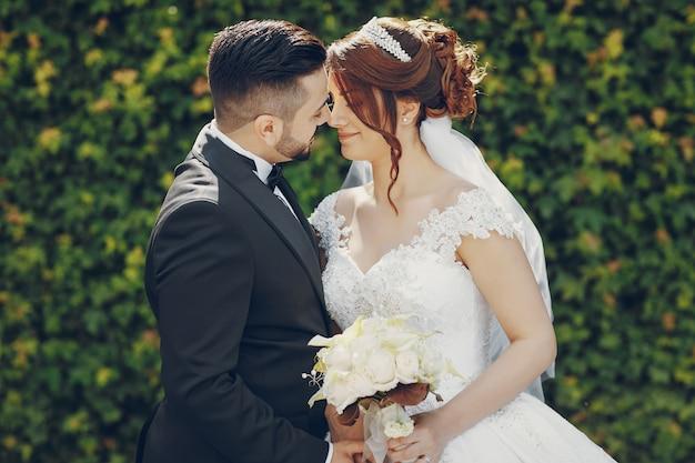 Un beau jeune homme portant un costume noir et une barbe dans le parc avec sa mariée