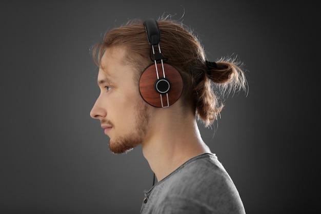 Beau jeune homme portant des écouteurs sur gris