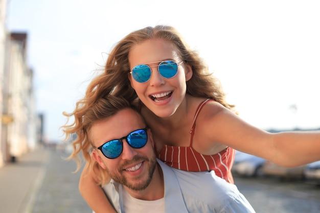 Beau jeune homme portant une jeune femme séduisante sur les épaules tout en passant du temps ensemble à l'extérieur.