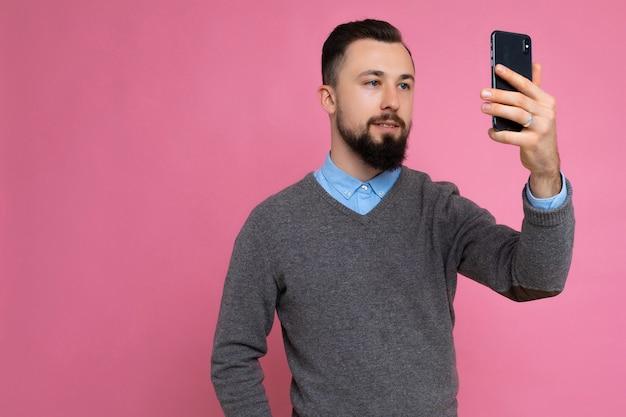 Beau jeune homme portant des vêtements élégants décontractés debout isolé sur fond mur tenant le smartphone prenant selfie photo regardant l'écran du téléphone mobile