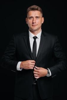 Un beau jeune homme porte un élégant costume noir et sourit sur fond noir. nettoyer, préparer.
