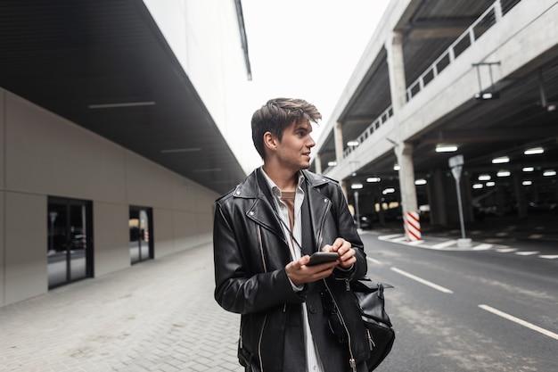 Beau jeune homme positif dans des vêtements en cuir noir surdimensionnés à la mode avec un sac à dos avec une coiffure avec un téléphone dans les mains et des sourires dans la rue de la ville. heureux gars dans la rue.