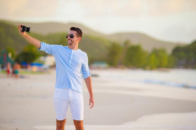 Beau jeune homme prenant une photo d'elle-même sur la plage tropicale