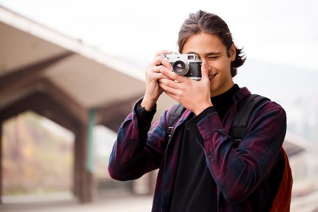 Beau jeune homme prenant une photo