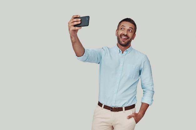 Beau jeune homme prenant selfie à l'aide d'un téléphone intelligent et souriant en se tenant debout sur fond gris